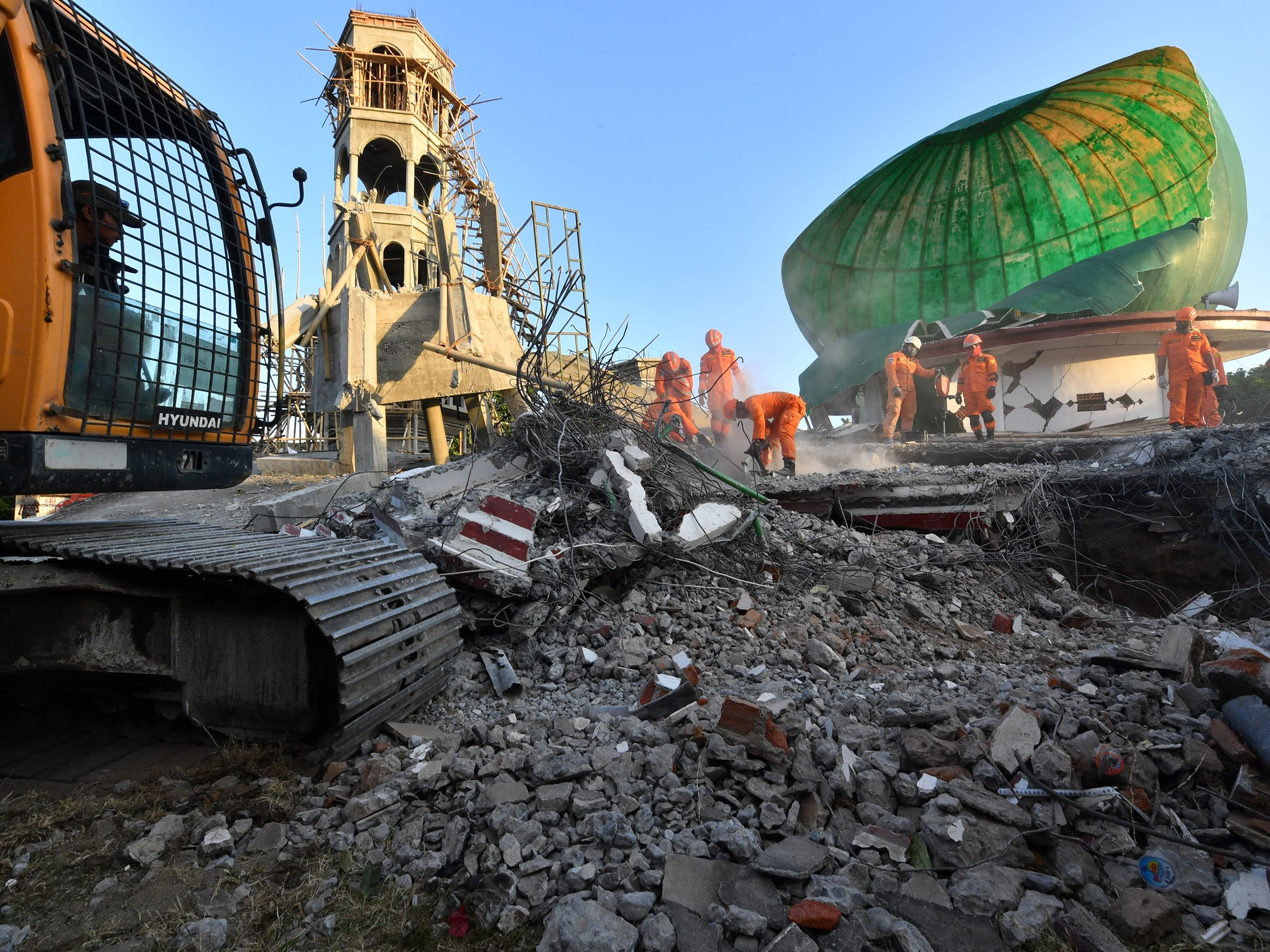 Indonesian search and rescue personnel work on a collapsed mosque in Pemenang, North Lombok on Aug. 6, 2018, the day after an earthquake struck the area.