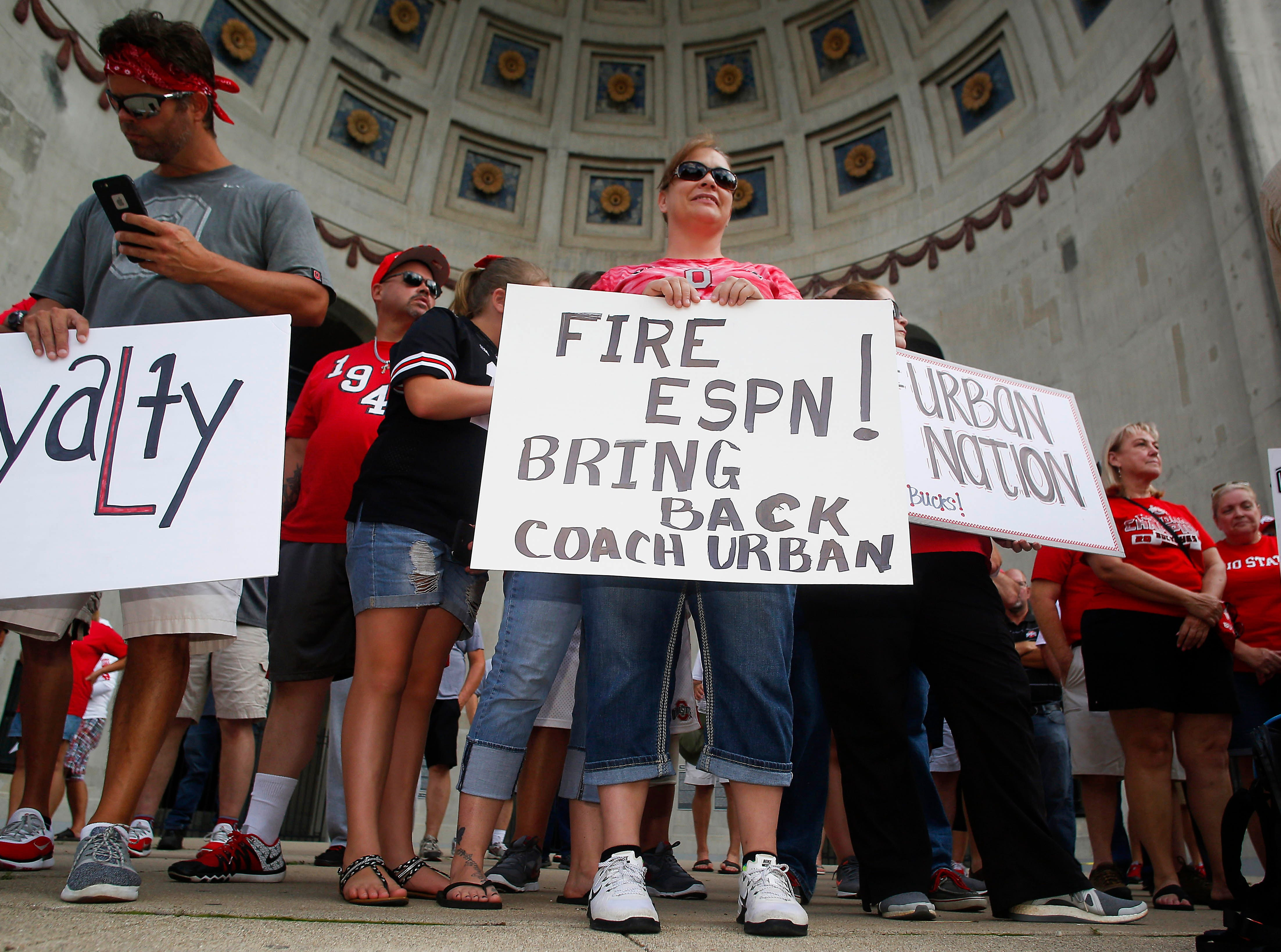 Tonya Poland of New Concord, Ohio, and others support Ohio State coach Urban Meyer at a rally held at Ohio Stadium.