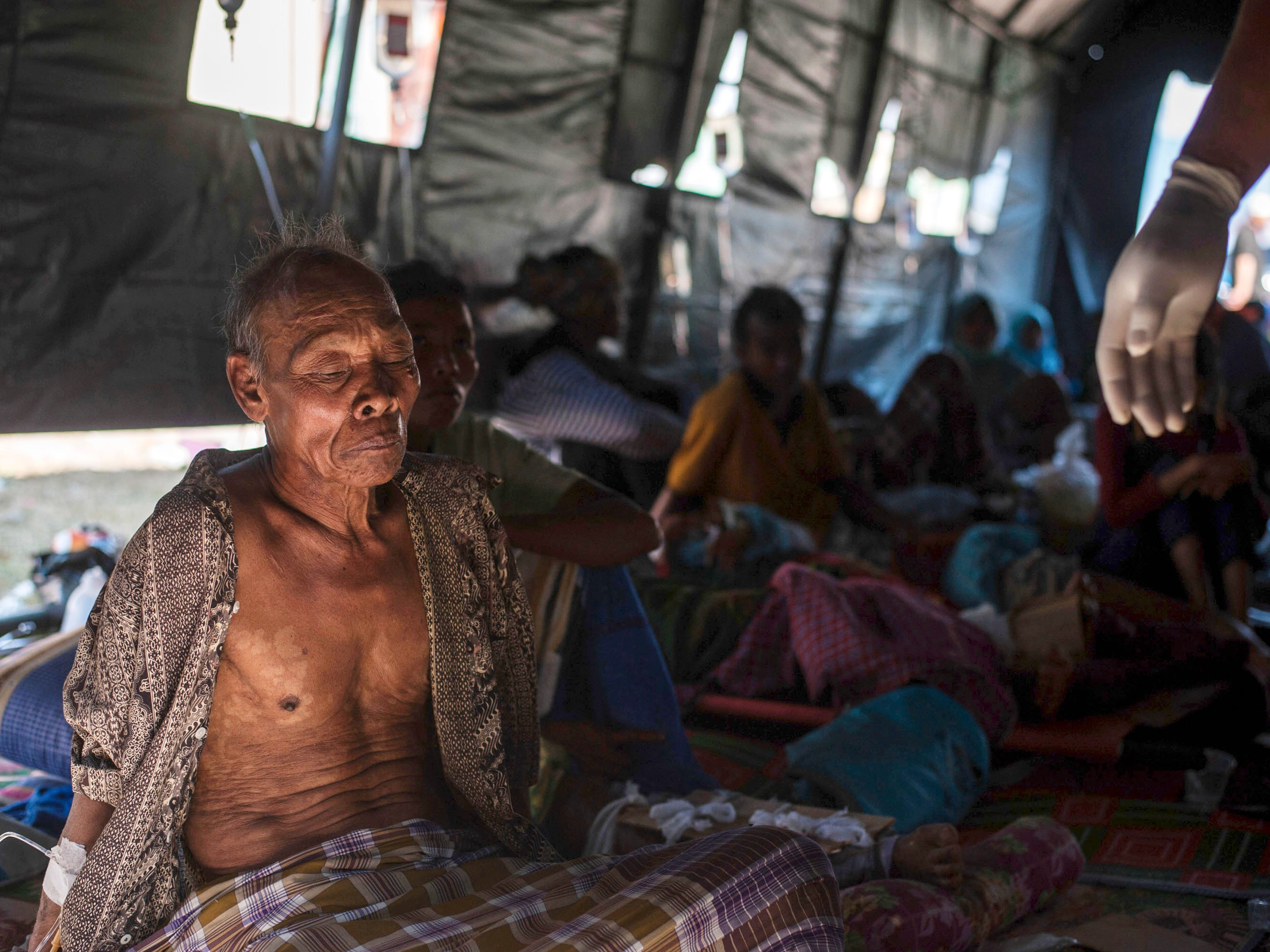 An elderly man rests in a makeshift hospital after surviving a major earthquake in Kayangan on Lombok Island, Indonesia, on Aug. 6, 2018.