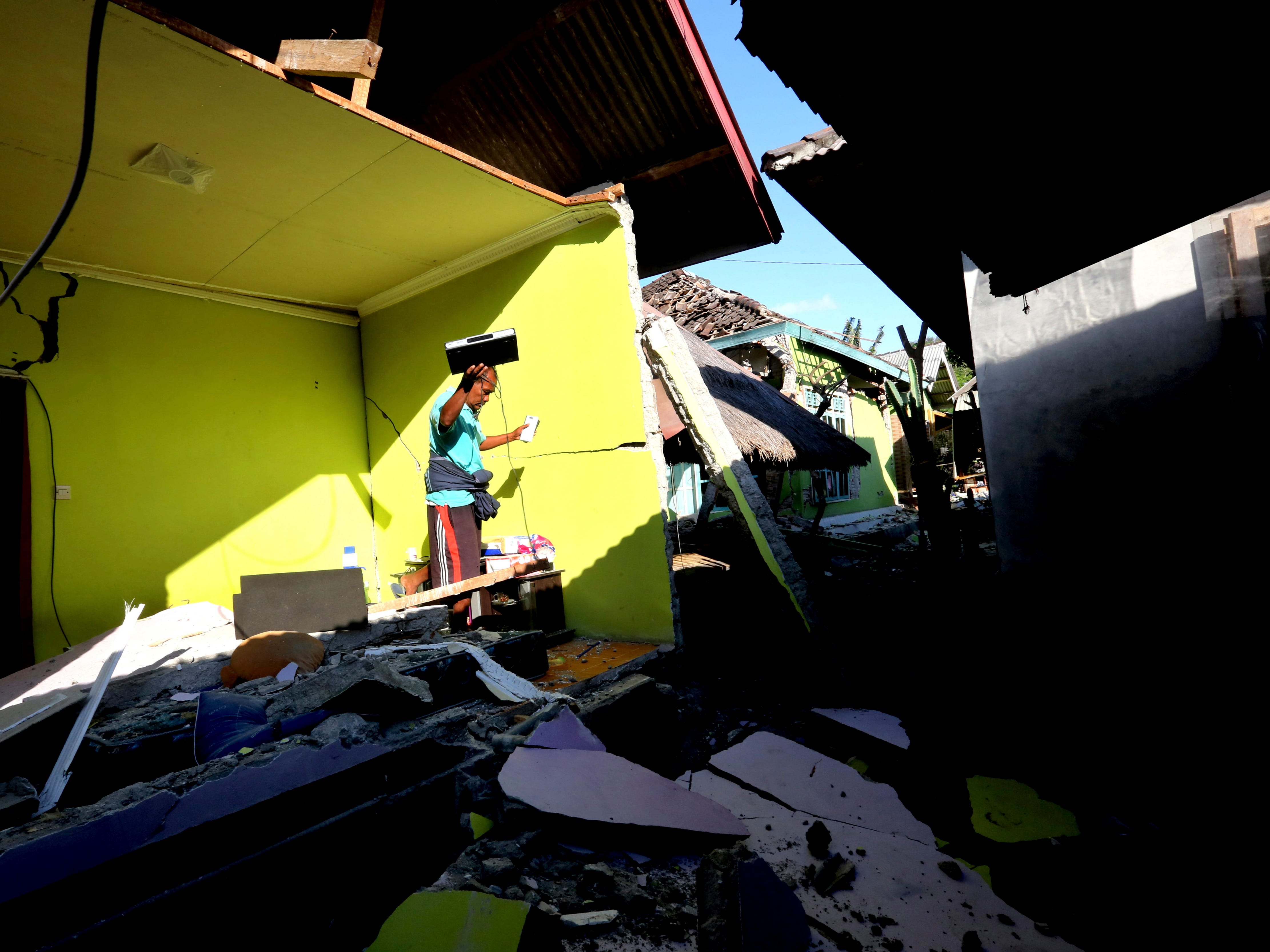 Usable items are salvaged from a home destroyed in an earthquake in North Lombok, Indonesia, on Aug. 6, 2018.