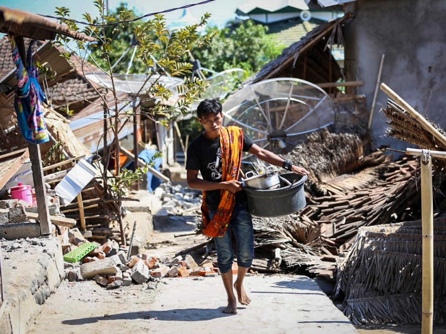 An Indonesian man collects his belongings from his collapsed house after an earthquake struck in North Lombok, West Nusa Tenggara, Indonesia, on Aug. 6, 2018.
