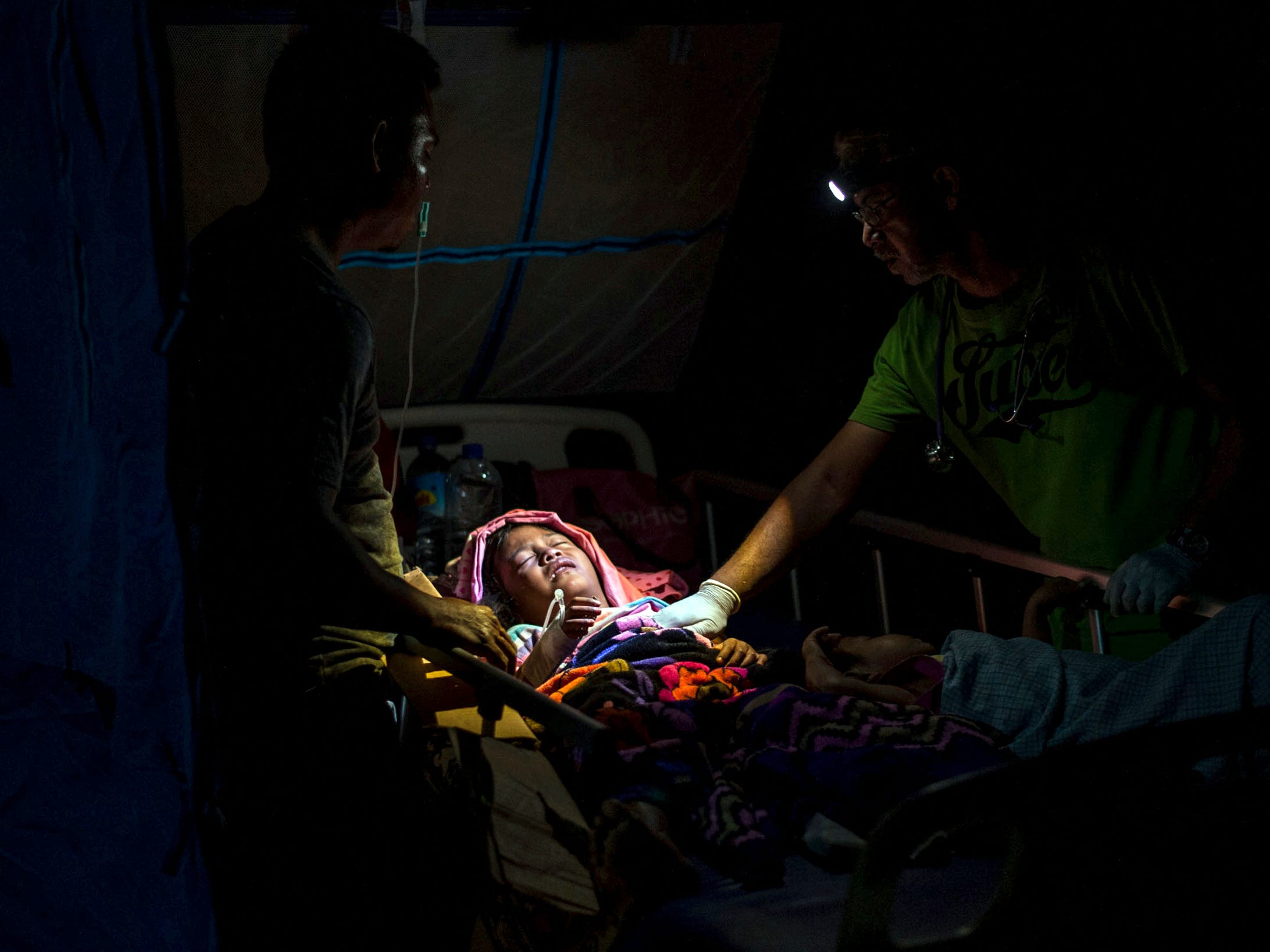 A doctor examines a child injured in the earthquake at a makeshift hospital in Tanjung on Lombok Island, Indonesia, on Aug. 6, 2018. The powerful earthquake flattened houses and toppled bridges on the Indonesian tourist island of Lombok, killing a large number of people and shaking neighboring Bali, as authorities said that rescuers still hadn't reached some devastated areas and the death toll would climb.