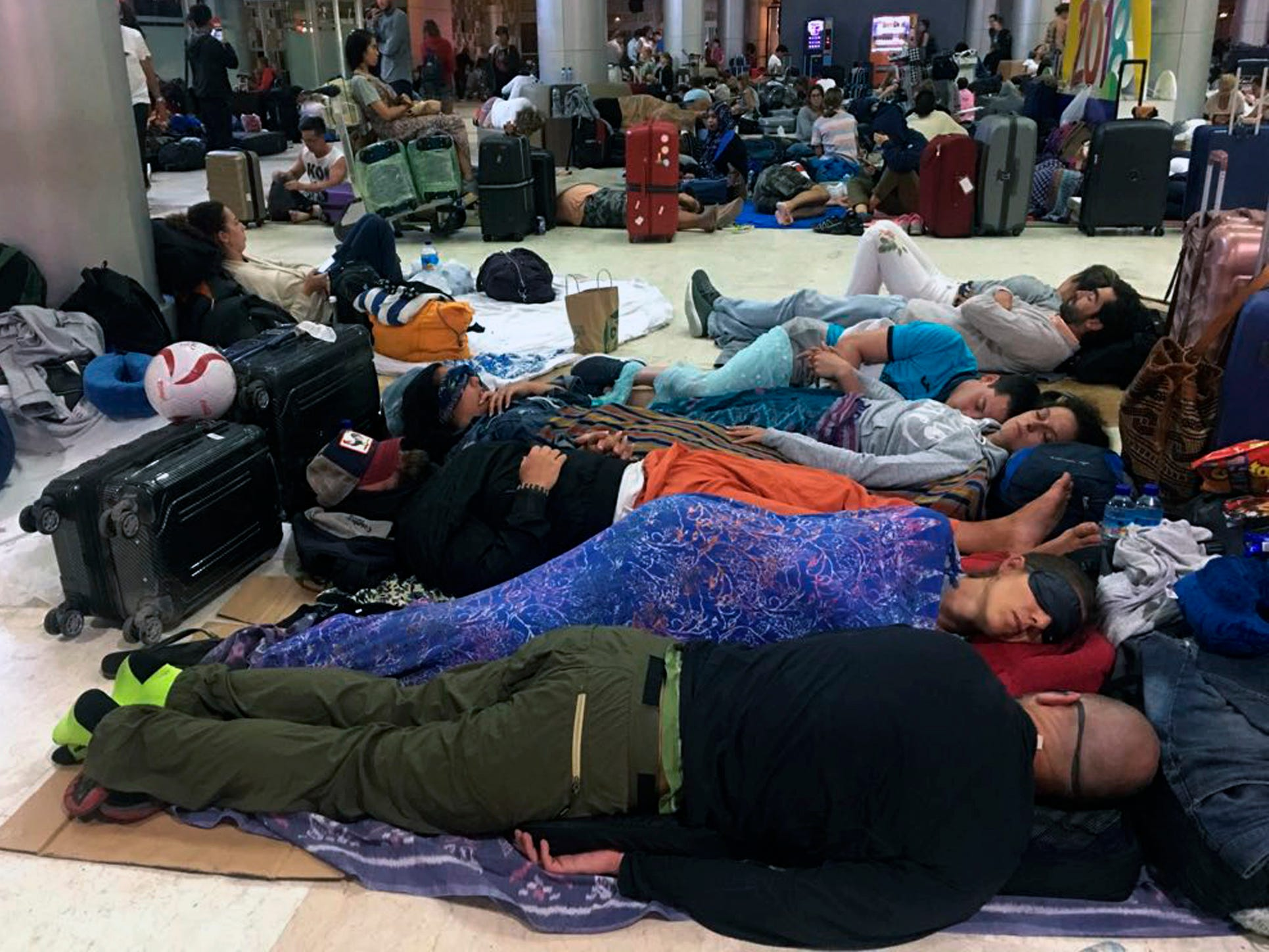 People sleep on the floor while stranded at Lombok International Airport following an earthquake in Praya, Lombok Island, Indonesia, Aug. 6, 2018.