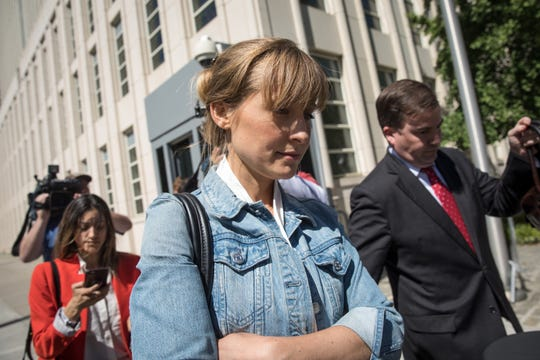 Allison Mack exits federal court in New York, June 12, 2018, after she was charged with sex trafficking in connection with alleged cult that forced women into sexual acts.