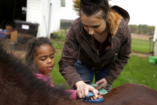 Moriah Rogowski helps a friend's daughter brush a pony outside of her parents' house in Mosinee.