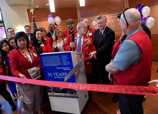 Kelly Jones of the Abilene Chamber of Commerce Redcoats hands Mike Murphy, CEO of Abilene Regional Medical Center, a pair of giant red scissor for cutting a ribbon and officially marking the 50th anniversary of the hospital Tuesday.