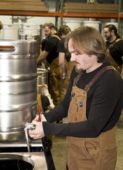 """Andrew Ashdown, a member of the first class of the Craft Beverage Institute of the Southeast at A-B Tech, makes beer in 2014. Students taste beer for flavor, and sometimes instructors add """"off"""" tastes so they can recognize problems, but students consume very little of the product they make."""
