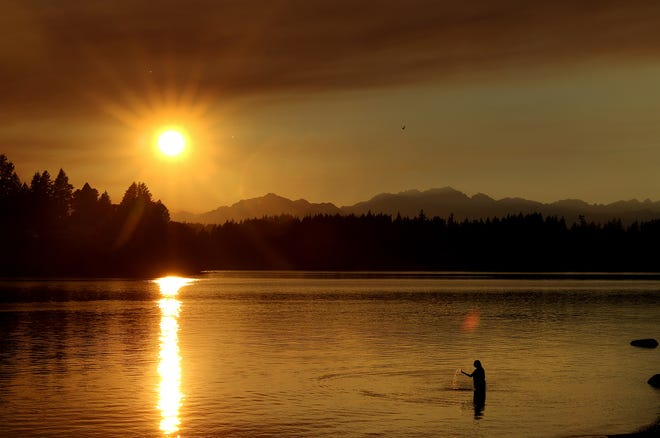 The sun sets through a haze, caused by smoke from wildfires, as seen from Lions Park in East Bremerton on Monday.