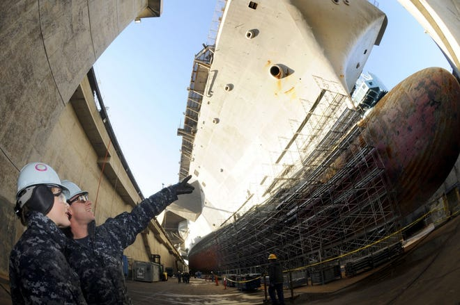 Aviation Boatswain's Mates (Handling) Airmen, Brianna Luttrell, from Bonanza, Ore., and Matthew Page, from Boston, view the aircraft carrier USS Ronald Reagan from the ground level of its dry dock. Ronald Reagan was in Bremerton, Wash., for a scheduled docked-planned incremental availability maintenance period in 2012.