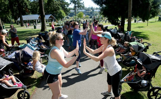 Jade Hart, left, of Kingston, and Samantha Hudspeth of Bremerton team up during the workout at the Fit4Mom Stroller Strides exercise class at Evergreen-Rotary Park in Bremerton.