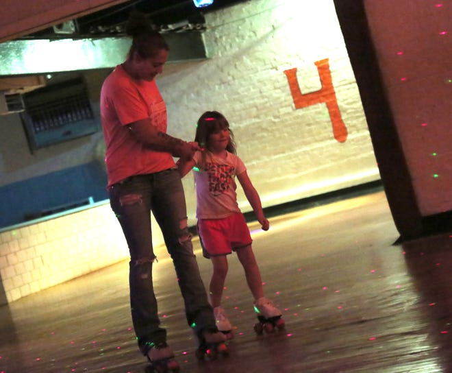 Katy McKinney holds the hand of Gabriella Flyn, 5, while rolling around the Sk8 Factory in Bucyrus for National Night Out on Tuesday.