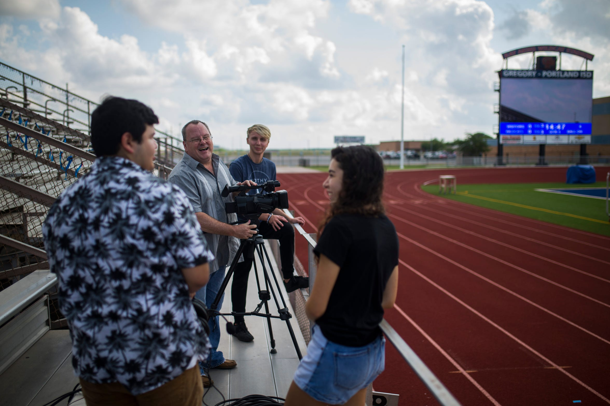 Brendan Opal, 17 (left),  David Rains, Zac Breaux, 17, and Anna Bella Villarreal, 17,  set up a camera to practice  for the upcoming football season, Friday August 3, 2018, at Ray Akins Wildcat Stadium.