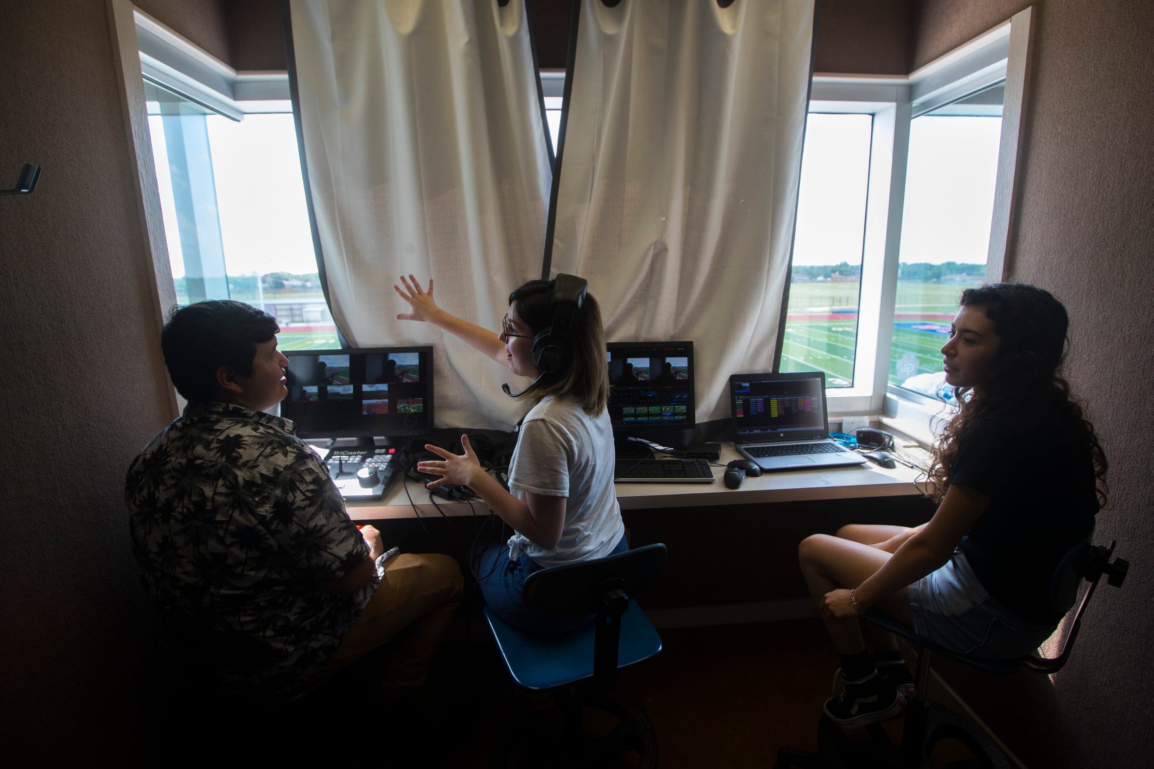 Gregory-Portland's Brendan Opal, 17 (left), Sara Maher, 17, and Anna Bella Villarreal work in the video booth to practice  for the upcoming football season, Friday August 3, 2018, at Ray Akins Wildcat Stadium.