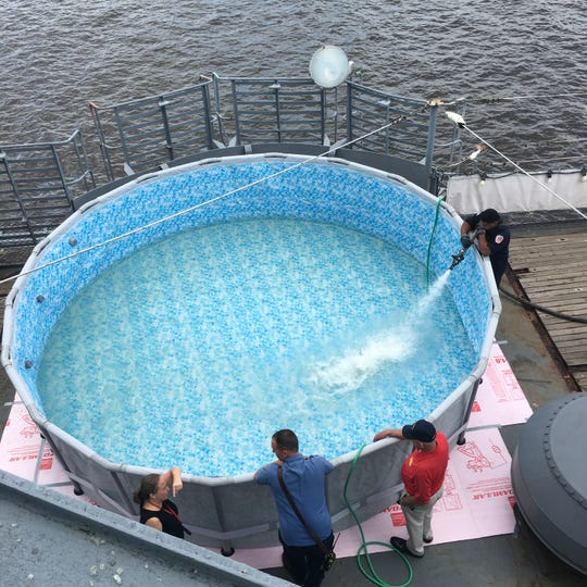 A Camden firefighter helps fill a swimming pool that has been installed on the deck of the Battleship New Jersey Museum and Memorial.