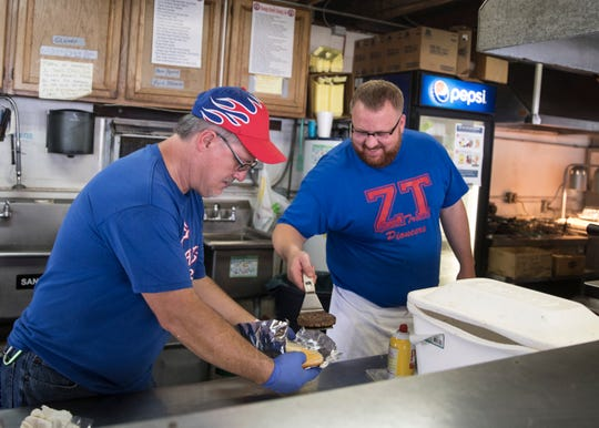 Workers inside the Zane Trace booster's food building wear gloves and handle the cooked food with tongs and spatulas to ensure food handling safety.