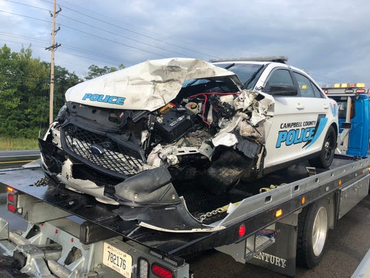 A tow truck hauls away a 2017 Ford police interceptor police say the driver of a stolen tractor trailer swerved across lanes on U.S. 27 to hit.