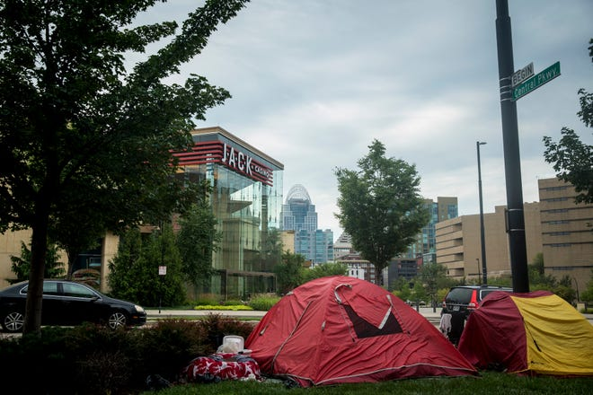 People move into tents along Central Parkway across from JACK Casino Tuesday, August 7, 2018, after an order from Judge Ruehlman closed a homeless camp on Third Street.