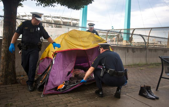 Cincinnati police officers check an abandoned tent along Third Street in downtown Cincinnati. As of this morning, August 7, the city is no longer allowing homeless to camp on the street, by order of Judge Robert Ruehlman. The request came from Hamilton County Prosecutor Joe Deters, who has filed a lawsuit against the city of Cincinnati. Things that can be salvaged, like the shoes at right, will be saved, everything else will be trashed.
