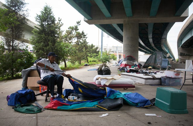 Edward Gordon, 58, recently from South Carolina, packs up his belongings from under the underpass near US Bank Arena. The city is no longer allowing homeless to camp along Third Street, including this area, by order of Judge Robert Ruehlman. The request came from Hamilton County Prosecutor Joe Deters, who has filed a lawsuit against the city of Cincinnati.