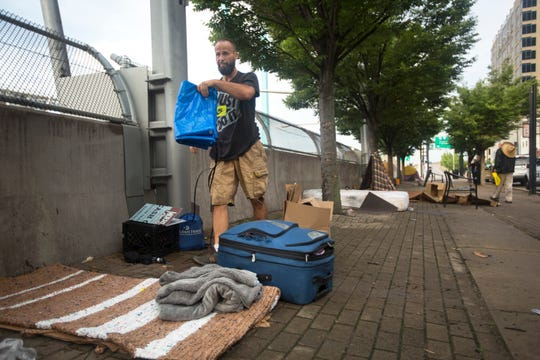 Chris Wynn, 40, originally from Amelia, packs up his tent and other belonging along Third Street in downtown Cincinnati. As of this morning, August 7, the city is no longer allowing homeless to camp on the street, by order of Judge Robert Ruehlman. The request came from Hamilton County Prosecutor Joe Deters, who has filed a lawsuit against the city of Cincinnati. Wynn said he has a job. He's trying to save money by living on the street.