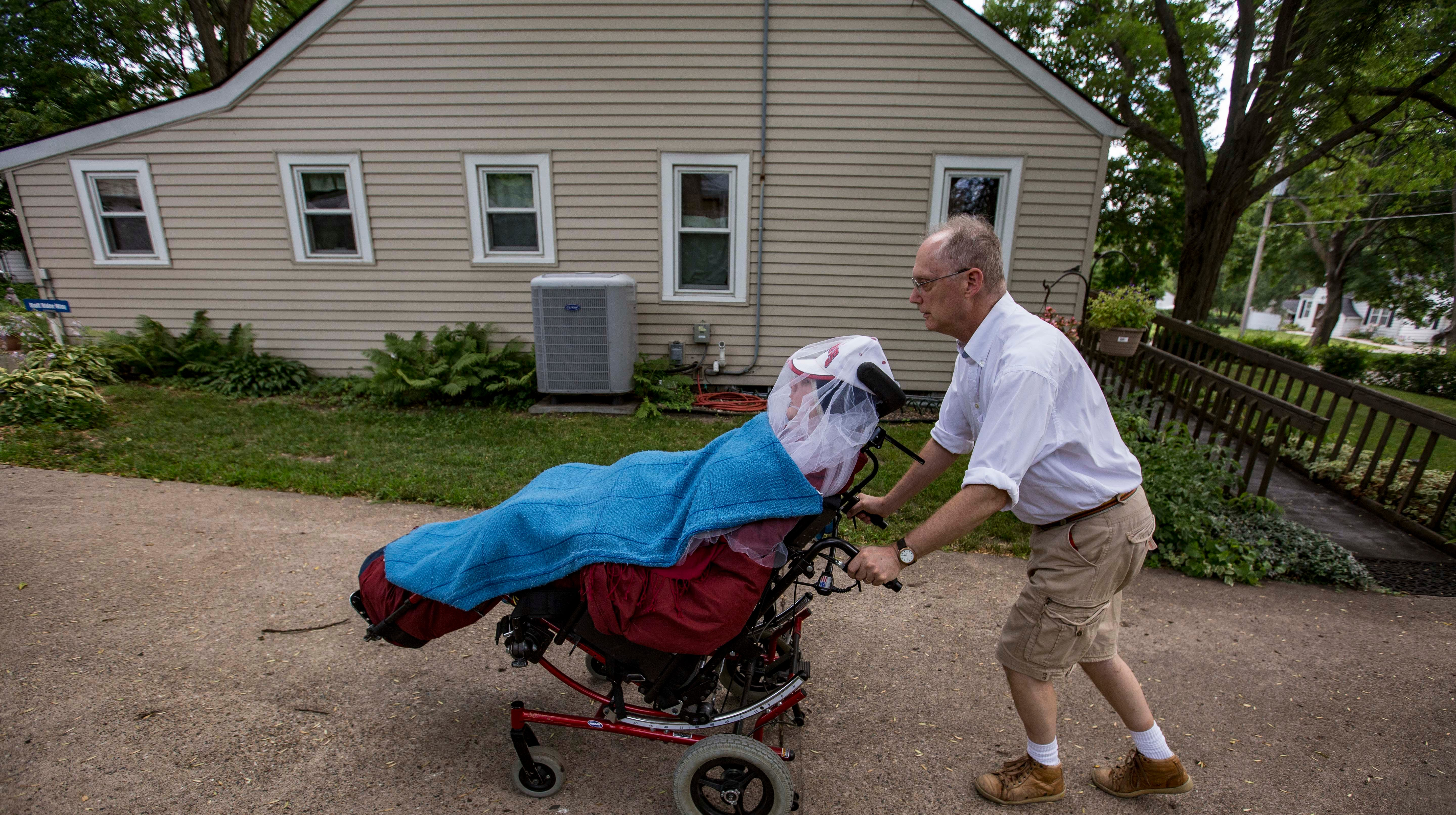 Matthew Hudson, 30, is wheeled outside at their home in Windsor Heights last month.
