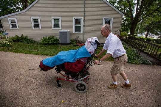 Medicaid recipient Matthew Hudson is wheeled outside his home in Windsor Heights recently.