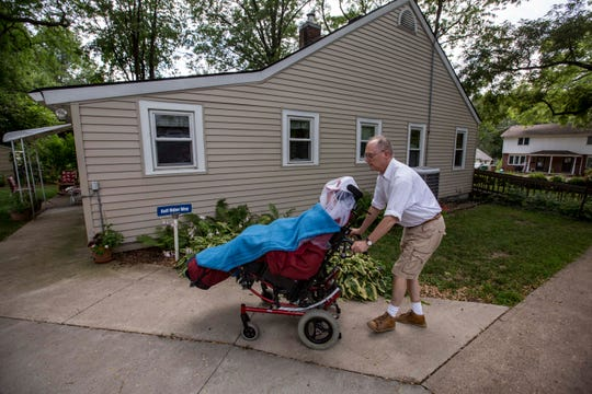 Matthew Hudson, 30, a Medicaid member with UnitedHealthcare coverage, is wheeled outside his Windsor Heights home by his father, David Hudson, in July 2018.