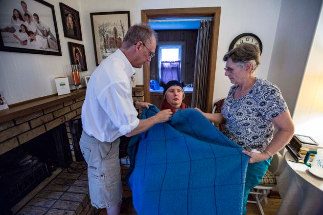 David and Mary Jo Hudson take care of their disabled son Matthew, 30, at their home in Windsor Heights last month. He cannot regulate his body temperature very well and is covered in blankets to help.