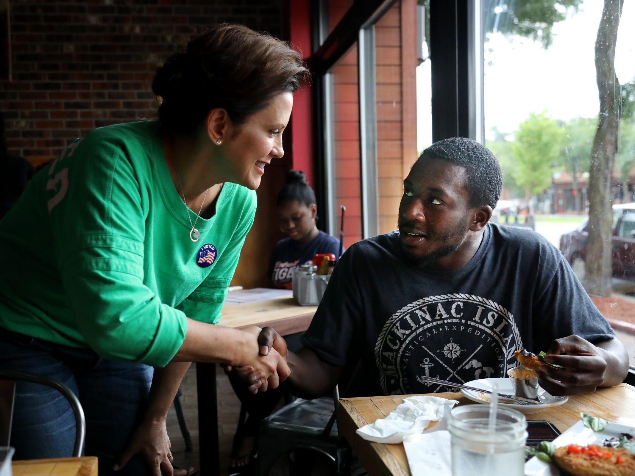 Gubernatorial Democratic Candidate Gretchen Whitmer shakes hands with prospective voter Jordan Dagnogo, 25, of Detroit at Kuzzo's Chicken and Waffles on the Livernois Avenue of Fashion on Michigan Primary day on Tuesday, Aug. 7, 2018.
