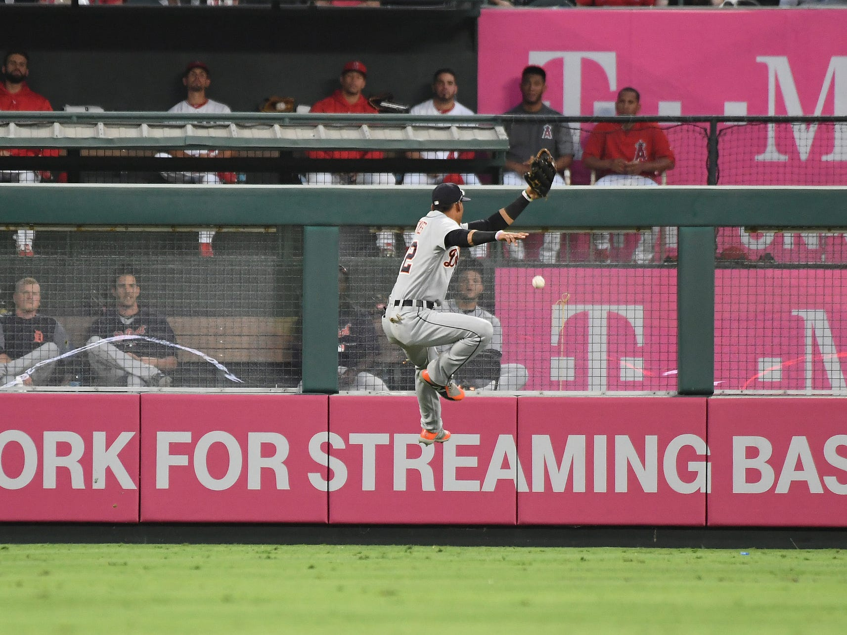 Tigers left fielder Victor Reyes (22) attempts to control the ball hit by Angels third baseman Kaleb Cowart (not pictured) for a run during the second inning on Monday, Aug. 6, 2018, in Anaheim, Calif.