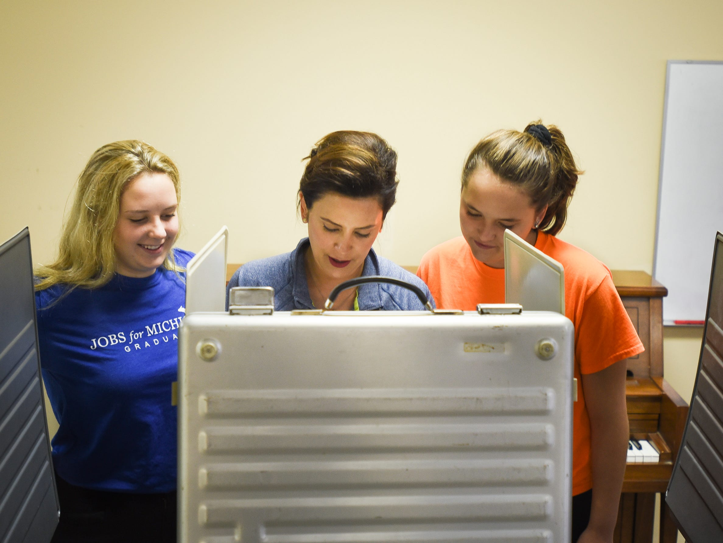 Flanked by daughters Sydney Shrewsbury, 14, left, and 11-year-old Sherry, Michigan democratic gubernatorial candidate Gretchen Whitmer fills out her ballot, Tuesday, Aug. 7, 2018, at St. Paul Lutheran church in East Lansing.