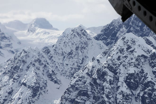 This April 24, 2016, file photo taken above the Kahiltna Glacier near Denali, shows peaks in the Alaska Range, as seen through the open cargo bay doors of a Chinook helicopter. Searchers said Monday, Aug. 6, 2018, that they found four people dead in a sightseeing airplane carrying Polish tourists in Alaska's Denali National Park a day and a half after thick clouds hampered the response to a distress call. Another person is missing and presumed dead after the crash Saturday evening.