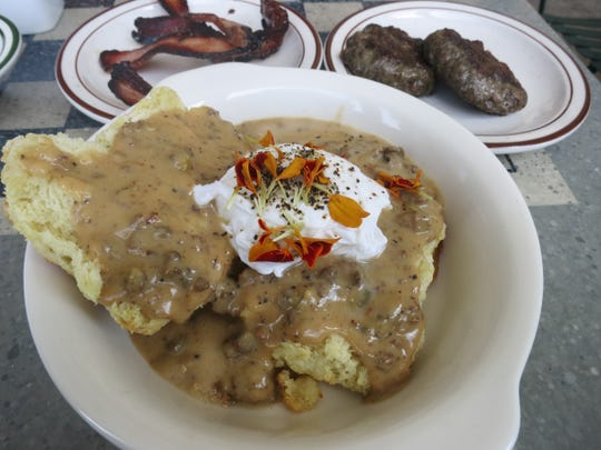 Parks & Rec's biscuits and gravy, made with three kinds of house-made sausage, are flanked by sides of house-cured bacon and pork sausage patties.