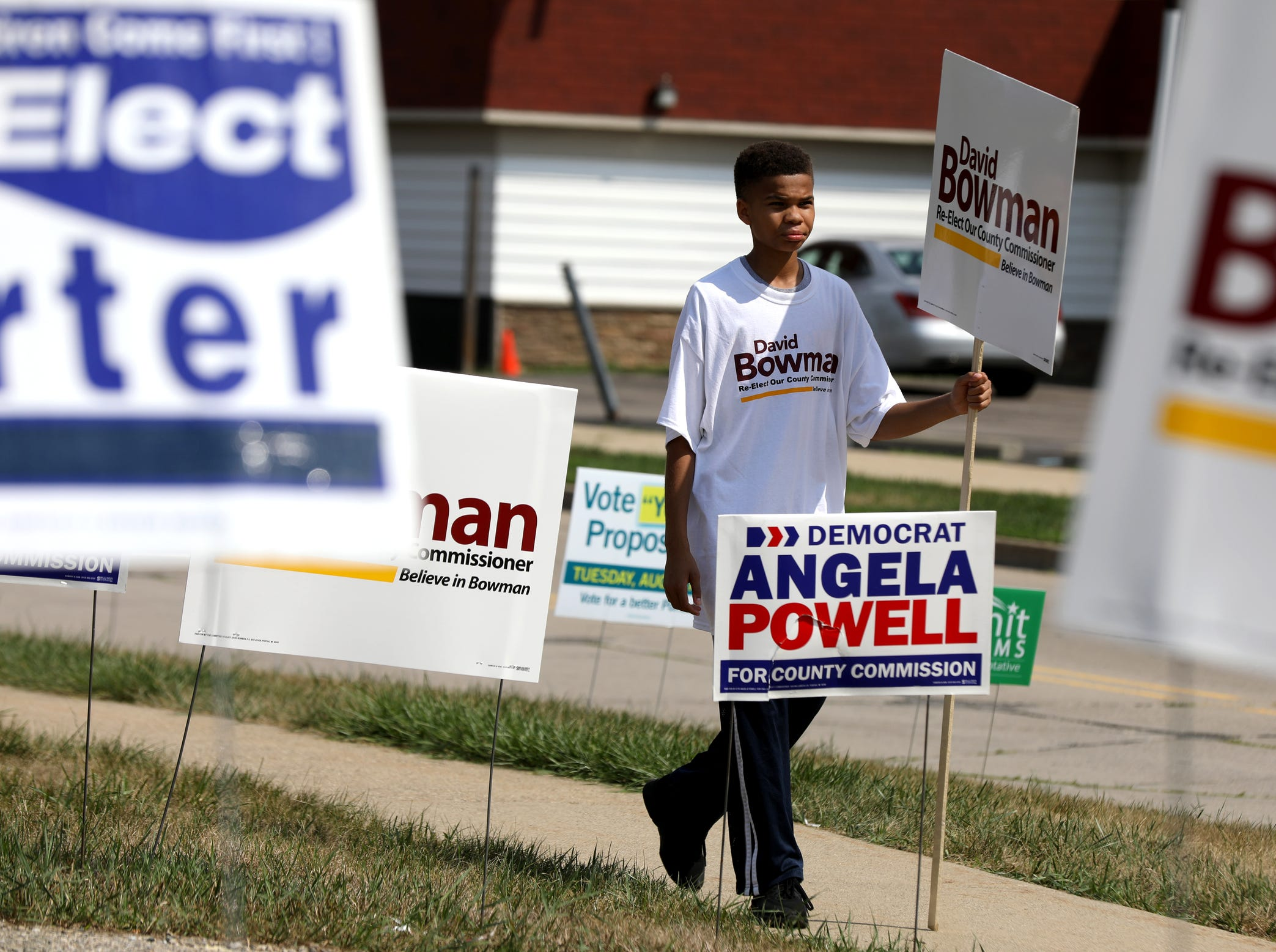 Josiah Elam, 13 of Pontiac carries a sign in support of a candidate while outside the  Bowens Center in Pontiac on Tuesday, August 7, 2018.