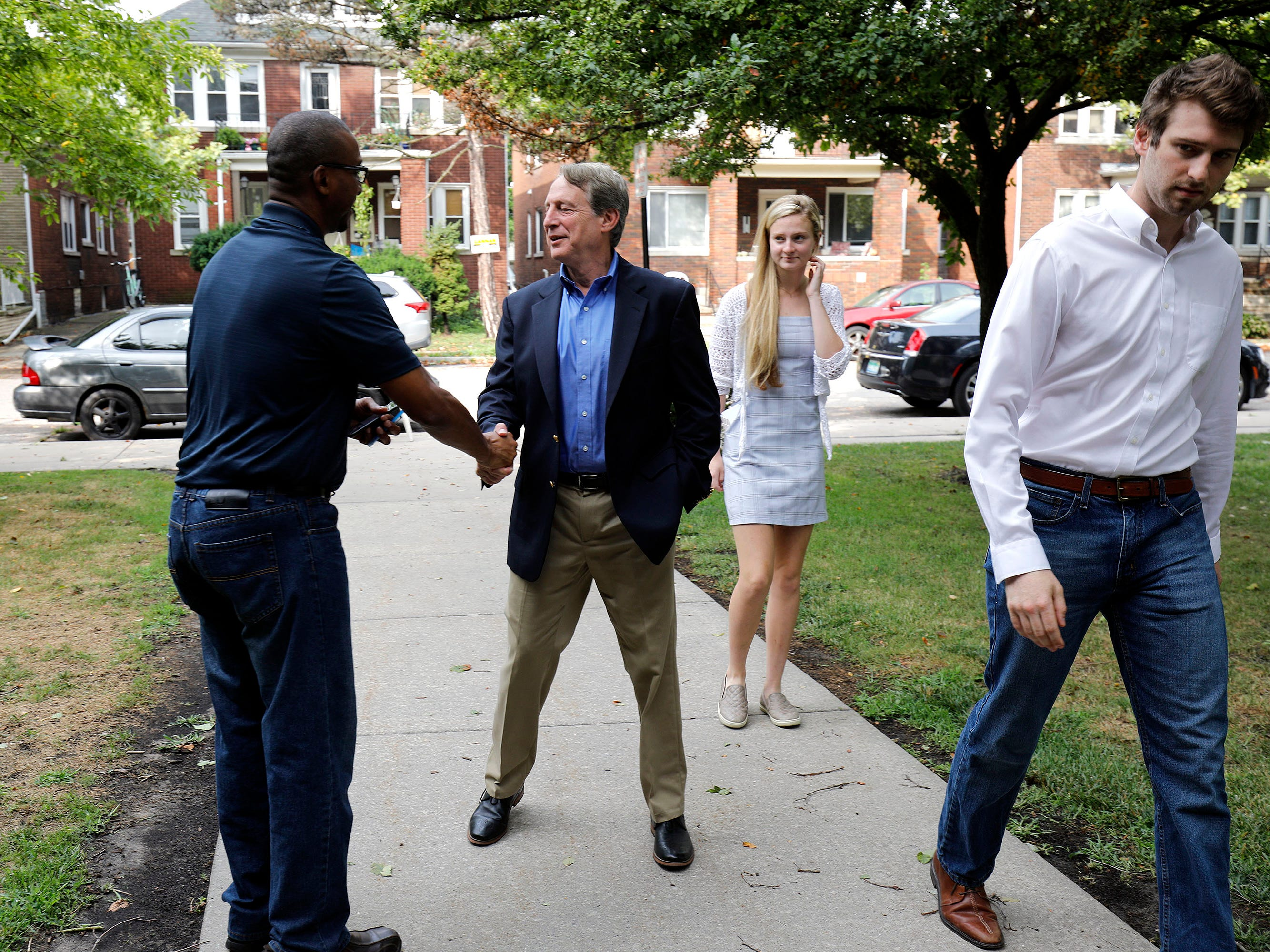 Sandy Pensler (center), Michigan Republican candidate for the U.S. Senate, greets a voter as he walks into his voting precinct accompanied by his son Jonathon and daughter Natasha to votes in the Michigan Primary election at Trombly School August 7, 2018 in Grosse Pointe Park, Michigan. Pensler's opponent, Republican John James, has received President Donald Trump's endorsement.