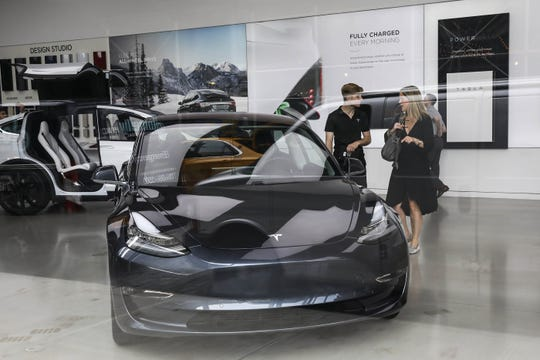 A customer is helped at a Tesla showroom in the Meatpacking District of Manhattan, August 7, 2018 in New York City.