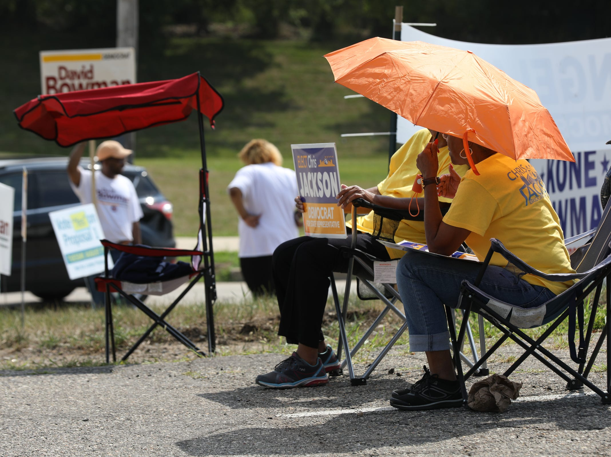 Political supporters attempt to stay cool in the hot sun while passing out pamphlets at the Bowens Center in Pontiac on Tuesday, August 7, 2018.