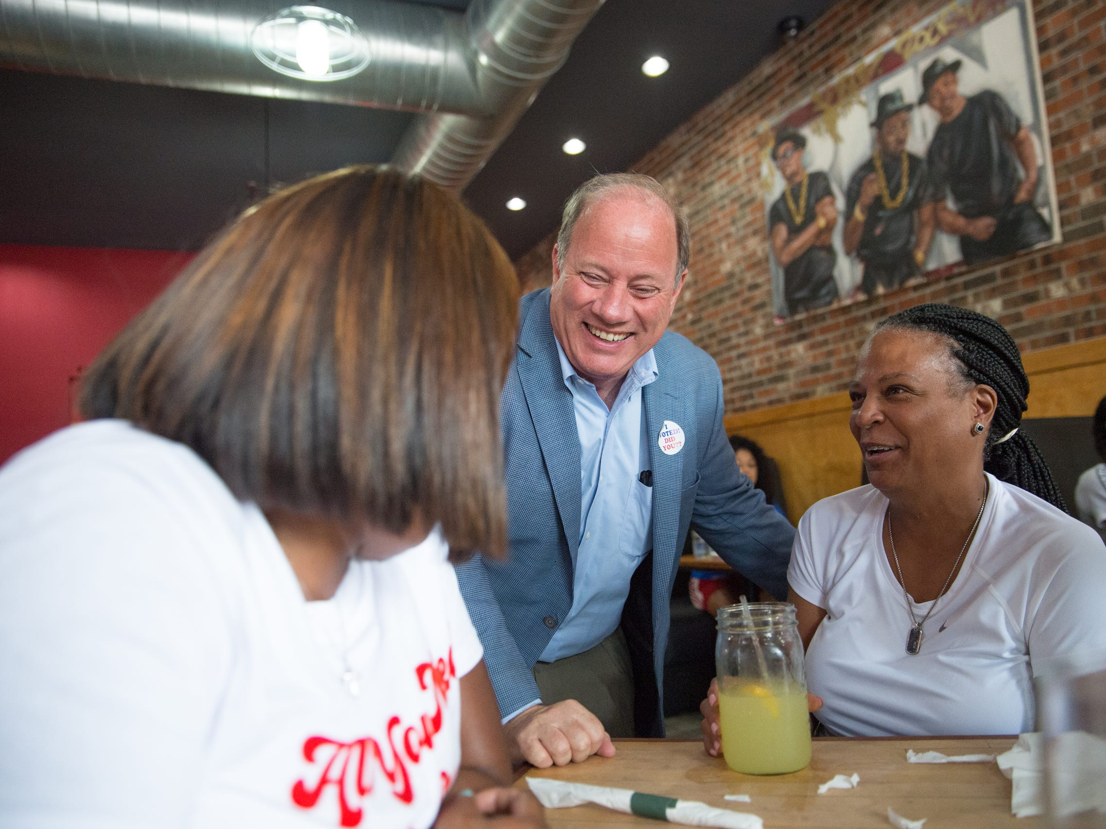 Detroit Mayor Mike Duggan speaks with Kai Bee and Monique David while campaigning on behalf of Gretchen Whitmer in Detroit on Aug. 8, 2018.