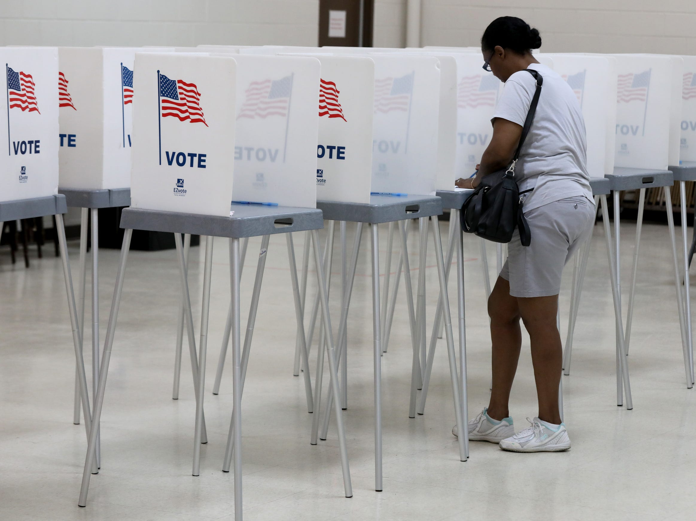 A woman casts her vote inside the gym of the Bowens Center in Pontiac on Tuesday, August 7, 2018.