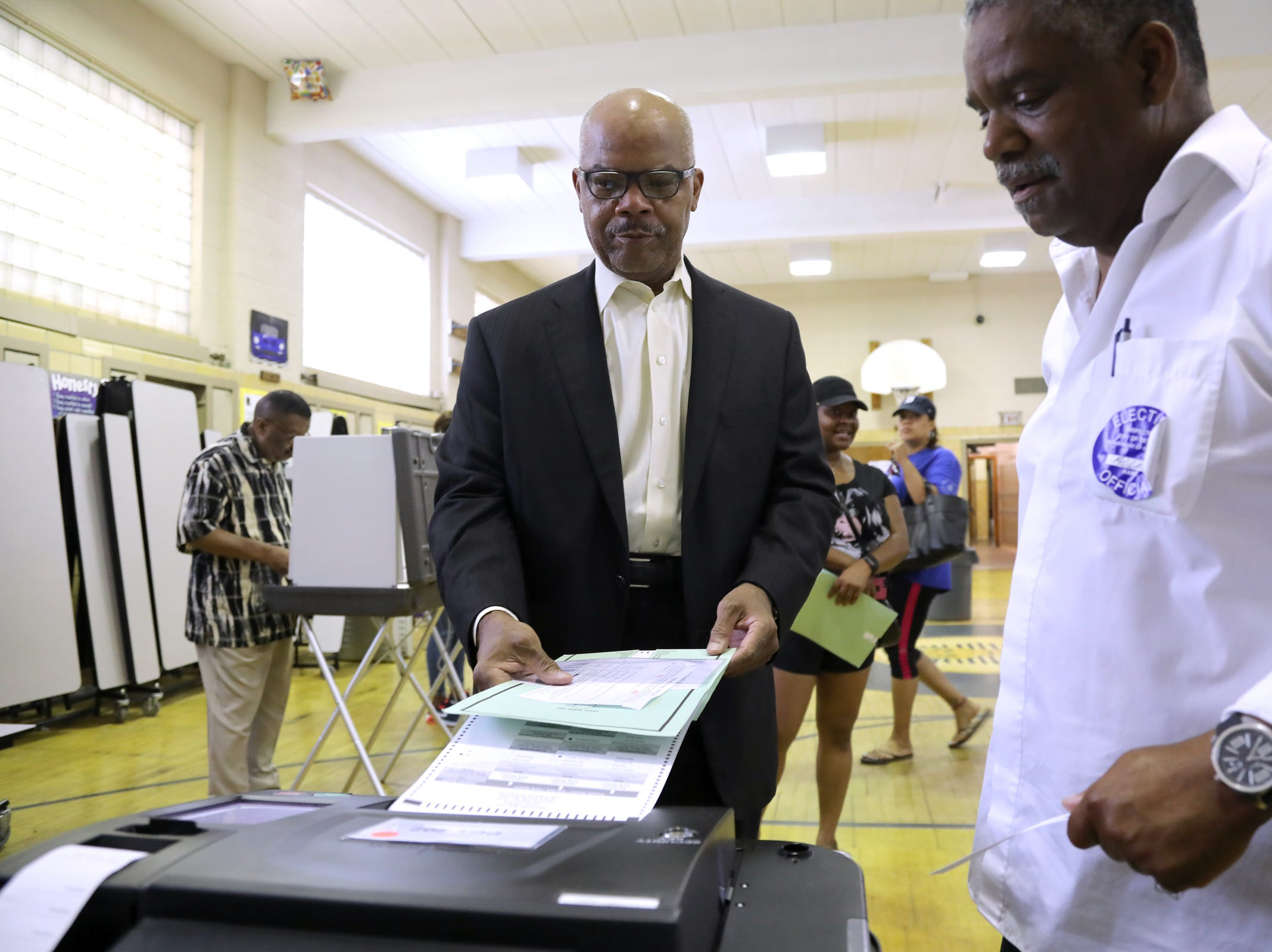 Greg Terrell, 65, who lives in the historic Sherwood Forest neighborhood of Detroit, casts his vote in the Michigan primaries with assistance from poll worker Alvin Lee, 62, of Detroit at Pasteur Elementary on Tuesday, Aug, 7, 2018.
