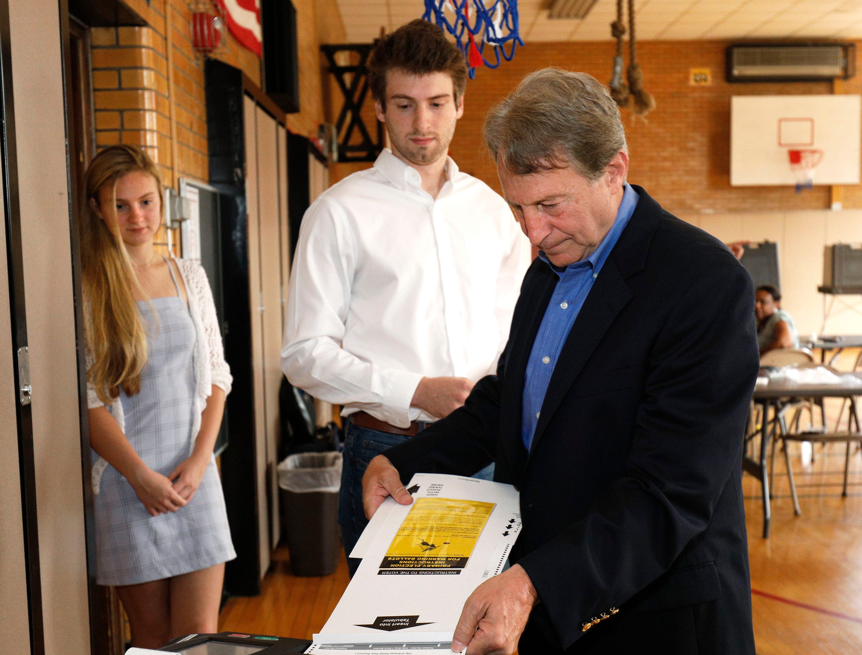 Sandy Pensler, Michigan Republican candidate for the U.S. Senate, puts his election ballot into the ballot machine while his son Jonathon and daughter Natasha watch as he votes in the Michigan Primary election at Trombly School August 7, 2018 in Grosse Pointe Park, Michigan. Pensler's opponent, Republican John James, has received President Donald Trump's endorsement.