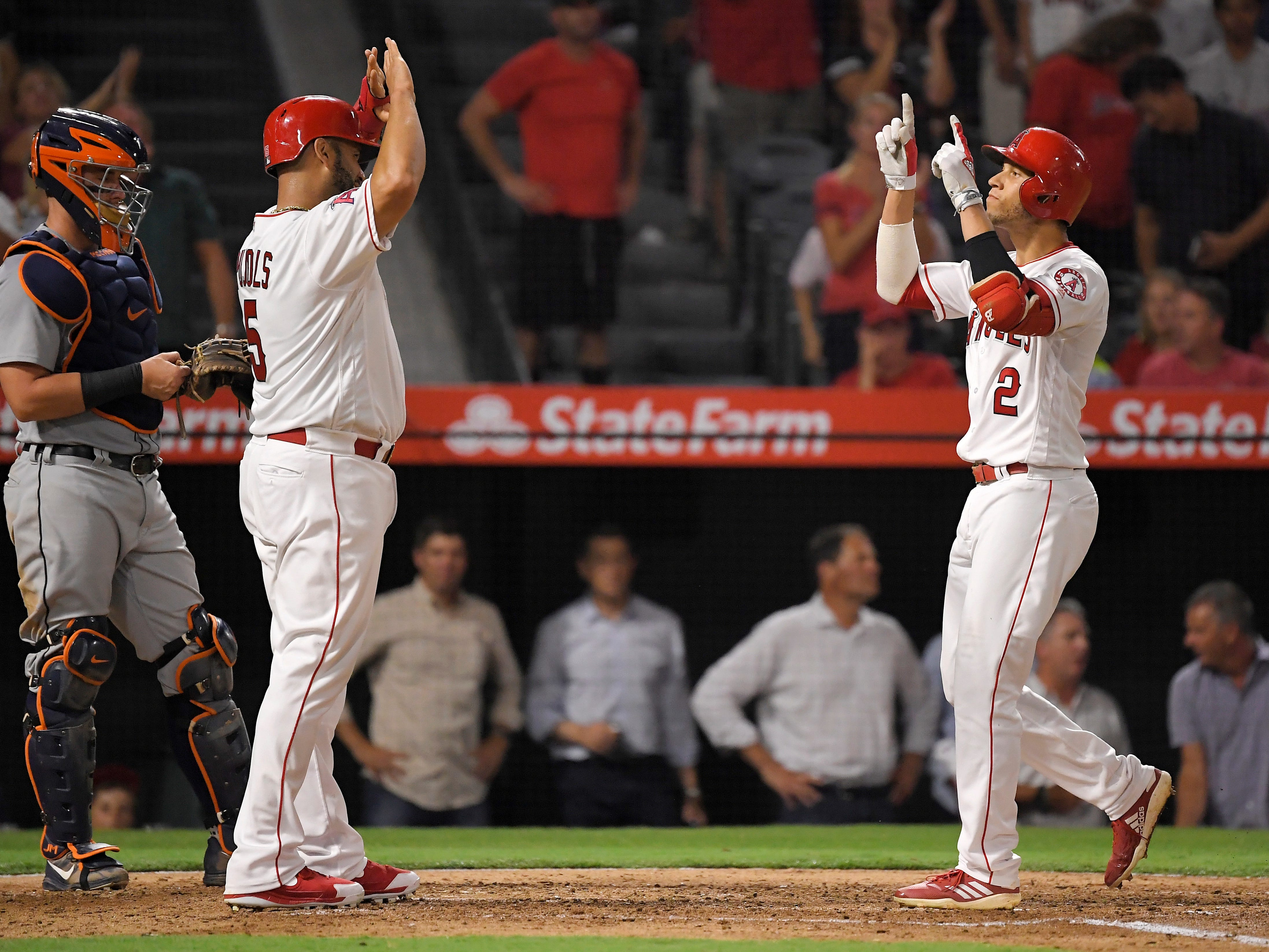 Los Angeles Angels' Andrelton Simmons, right, celebrates with Albert Pujols, center, after hitting a two-run home run during the fourth inning.