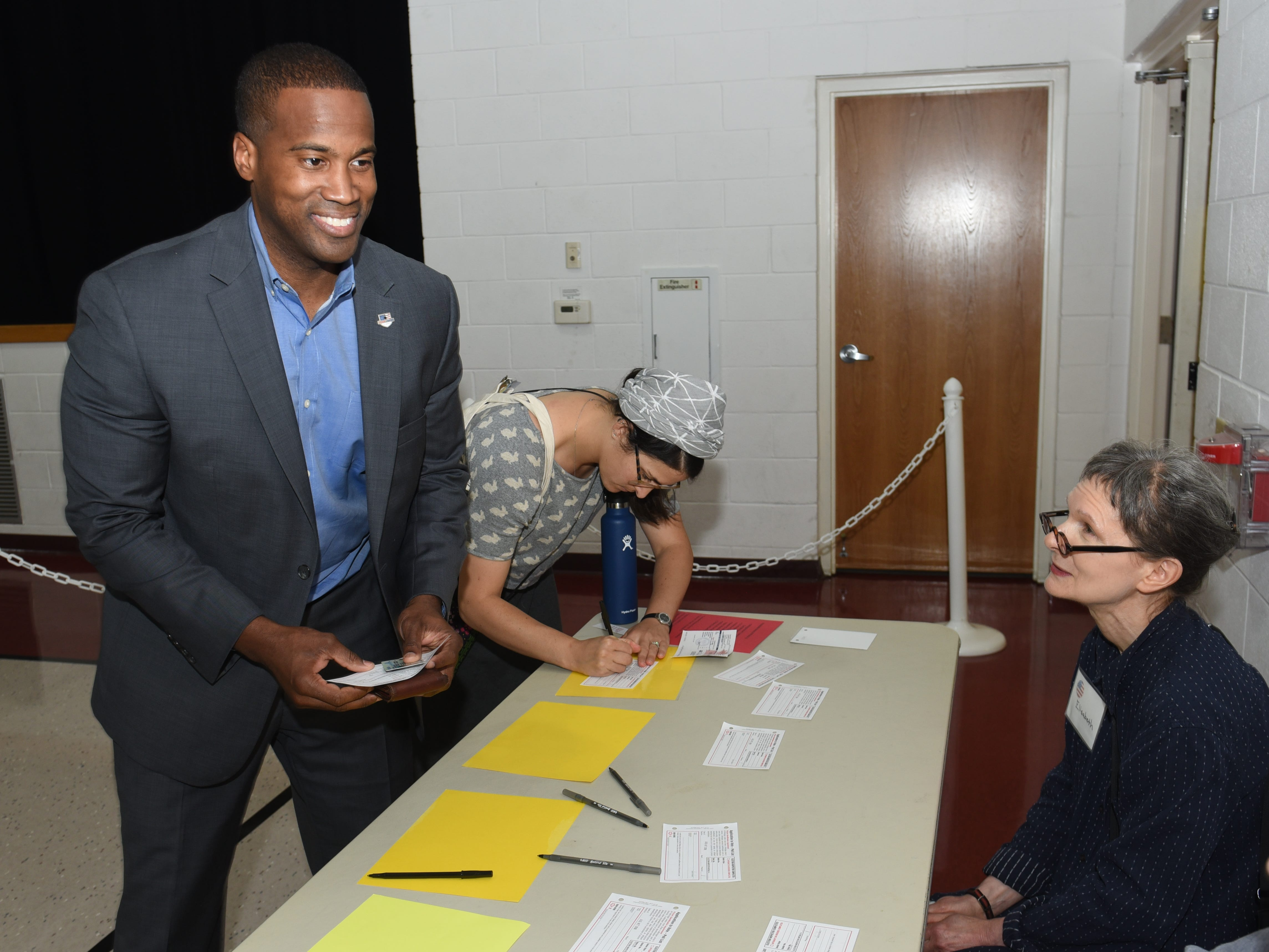 Republican U.S. Senate candidate John James fills out information to receive his ballot at Orchard United Methodist Church in Farmington Hills.