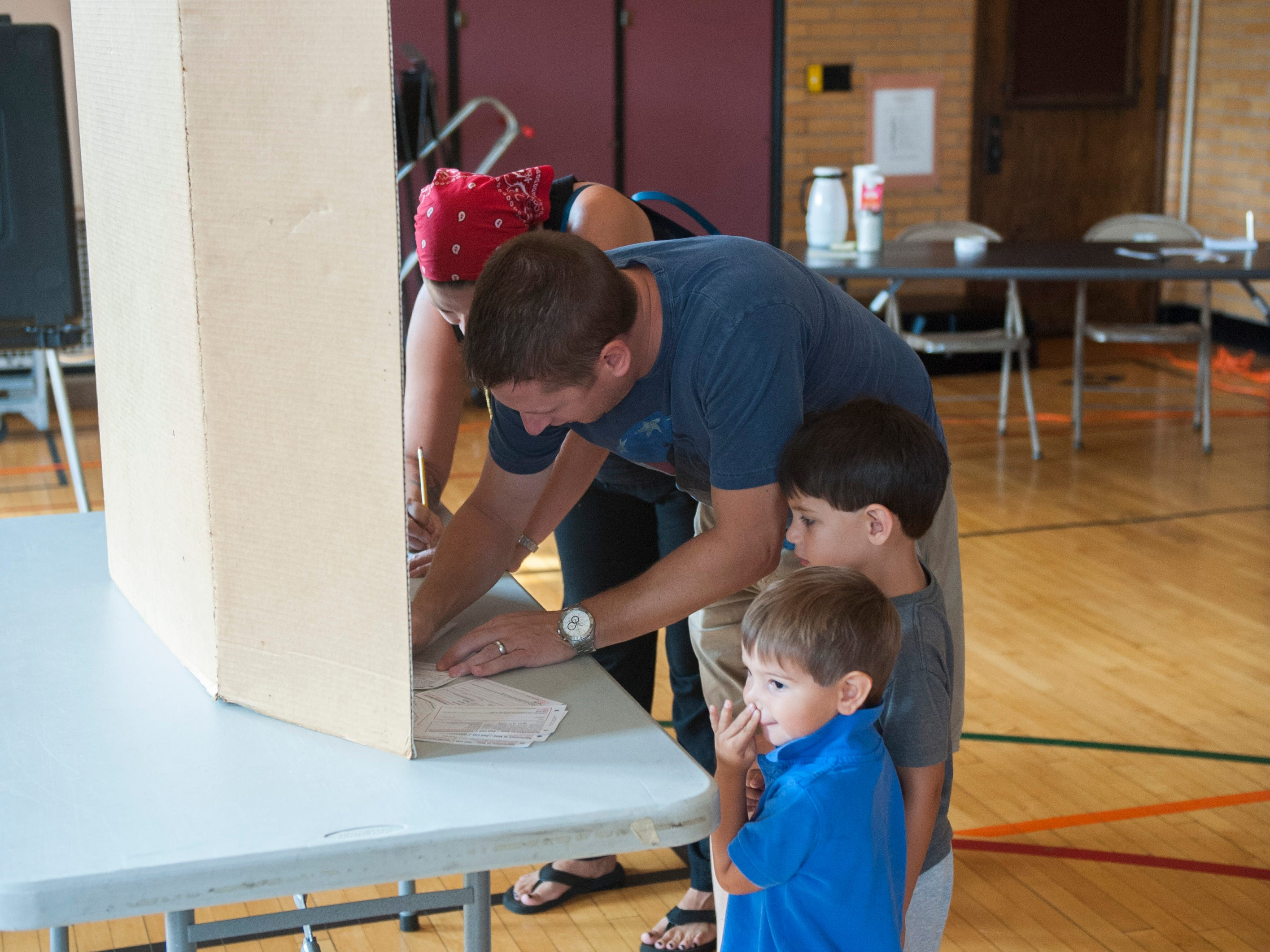 Chris D'Angelo and Elisa Gurule, Grosse Pointe Park, and their sons Francisco, 2, and Felix, 4, check in and fill out voting cards before  getting their primary election ballots at Trombly School in Grosse Pointe Park on Michigan's primary election day,  Tuesday, August 7, 2018. (John T. Greilick, The Detroit News)