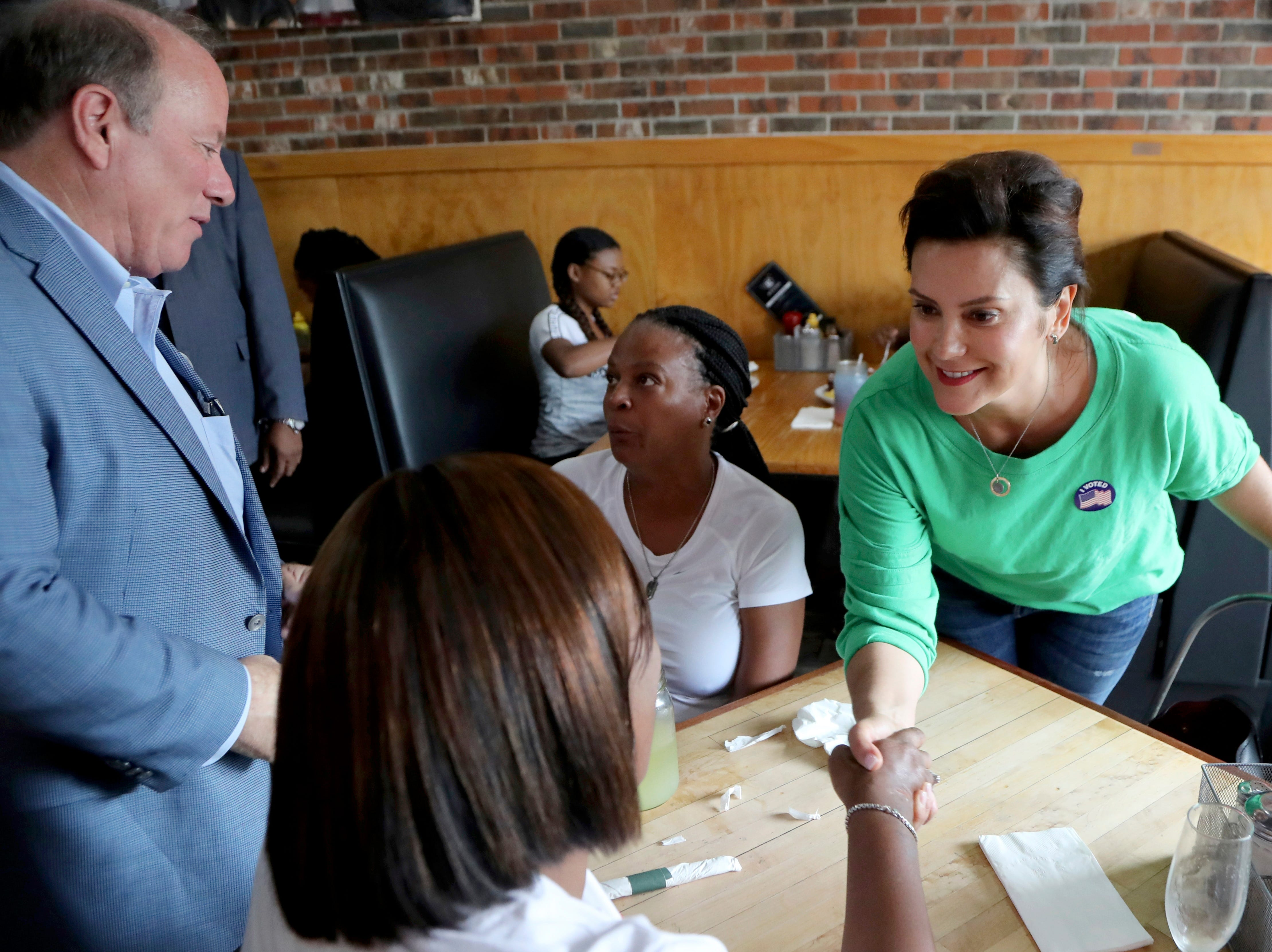 Michigan Democratic gubernatorial candidate Gretchen Whitmer and Detroit Mayor Mike Duggan visit with patrons at a restaurant on the city's north side, Tuesday, Aug. 7, 2018, in Detroit.