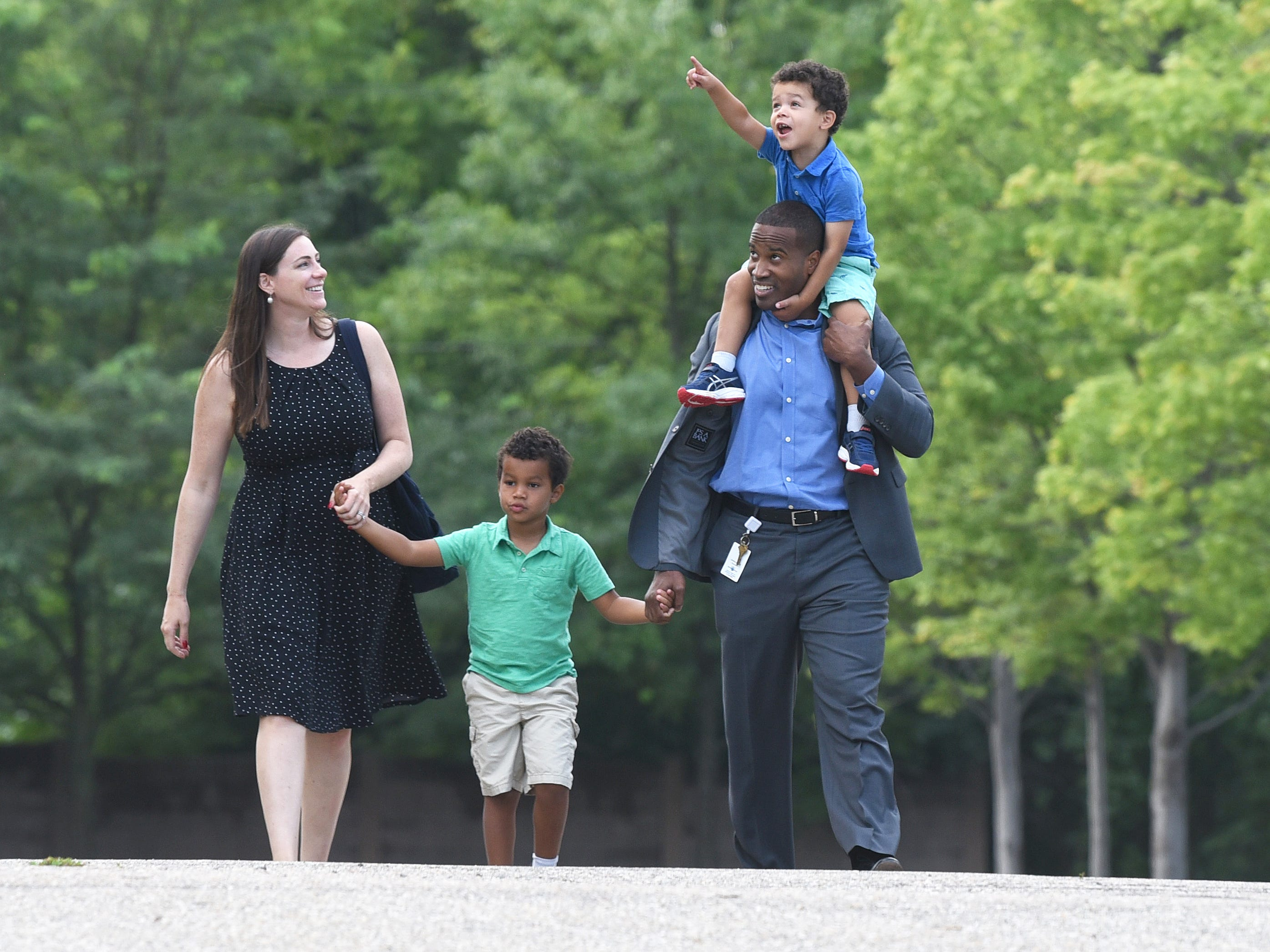 U.S. Senate candidate John James carries his son Hudson on his shoulders and walks toward the voting precinct with his wife Elizabeth and son John on Tuesday, August 7, 2018 at Orchard United Methodist Church in Farmington Hills.