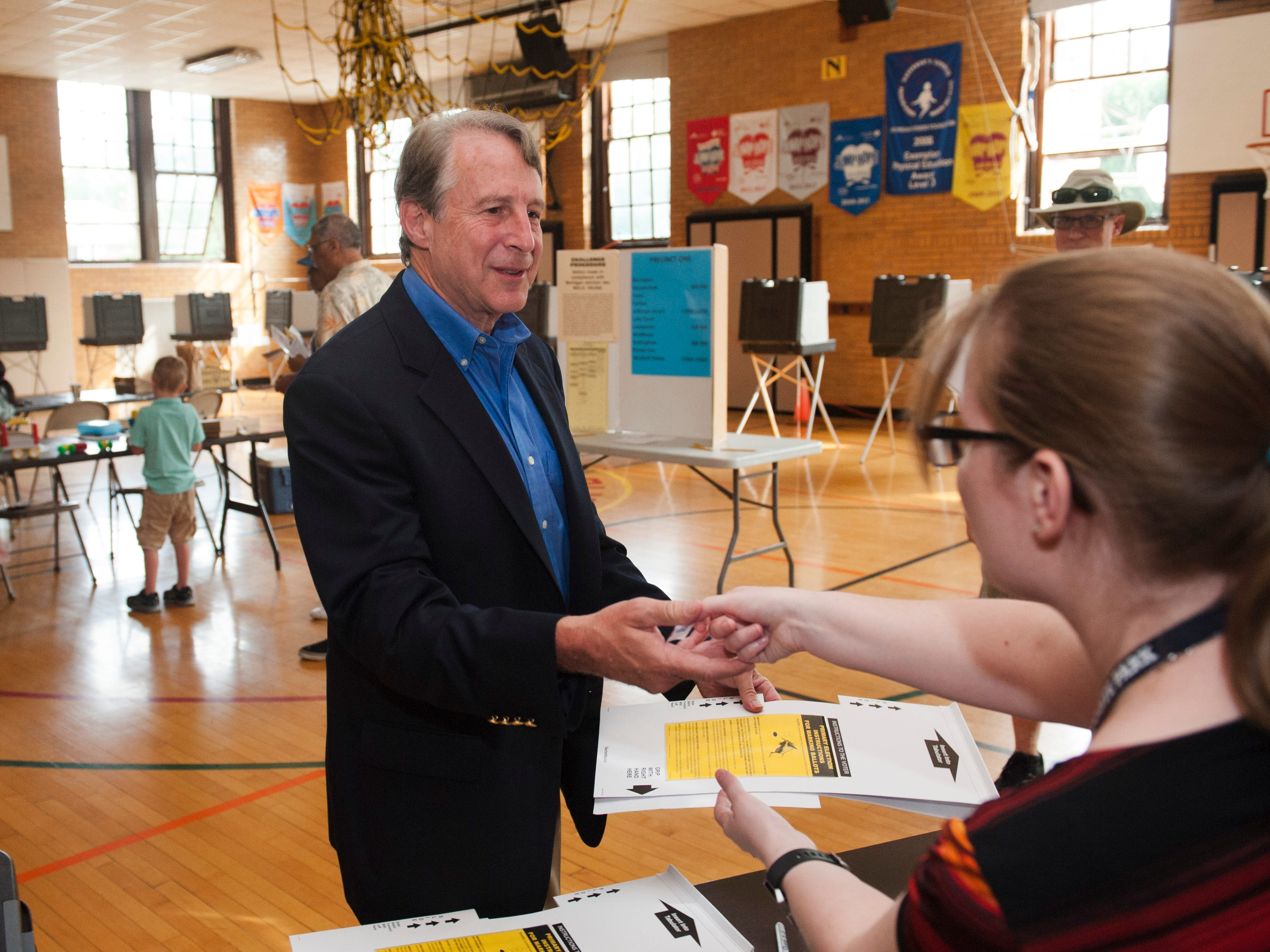 Grosse Pointe financier and candidate Sandy Pensler, who is running for the GOP U.S. Senate nomination, thanks election worker Courtney Delmege after casting his ballot in the Michigan primary election at Trombly School in Grosse Pointe Park.