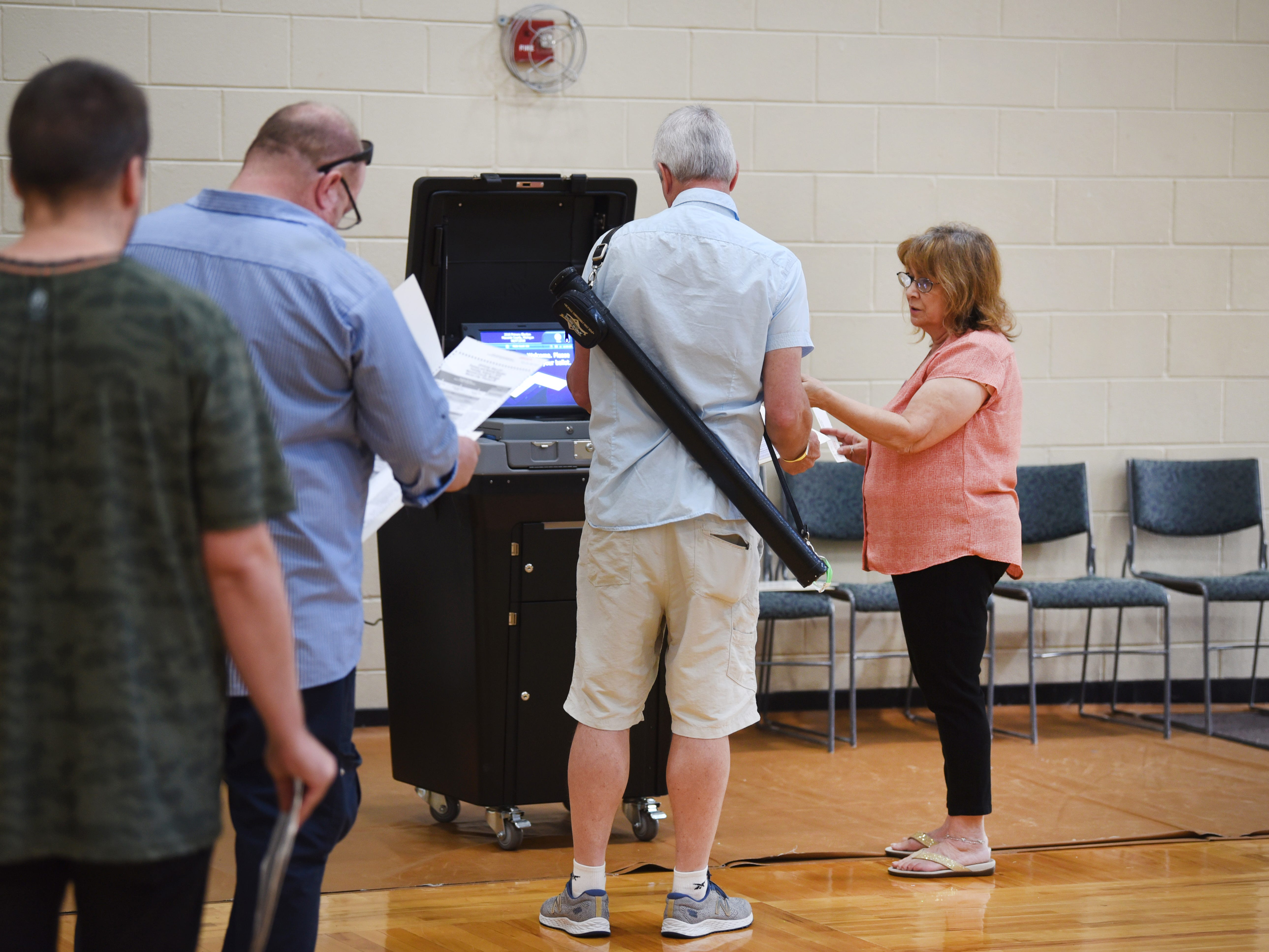 Voters file their ballots at the electronic voting machine at the Warren Community Center in Warren.