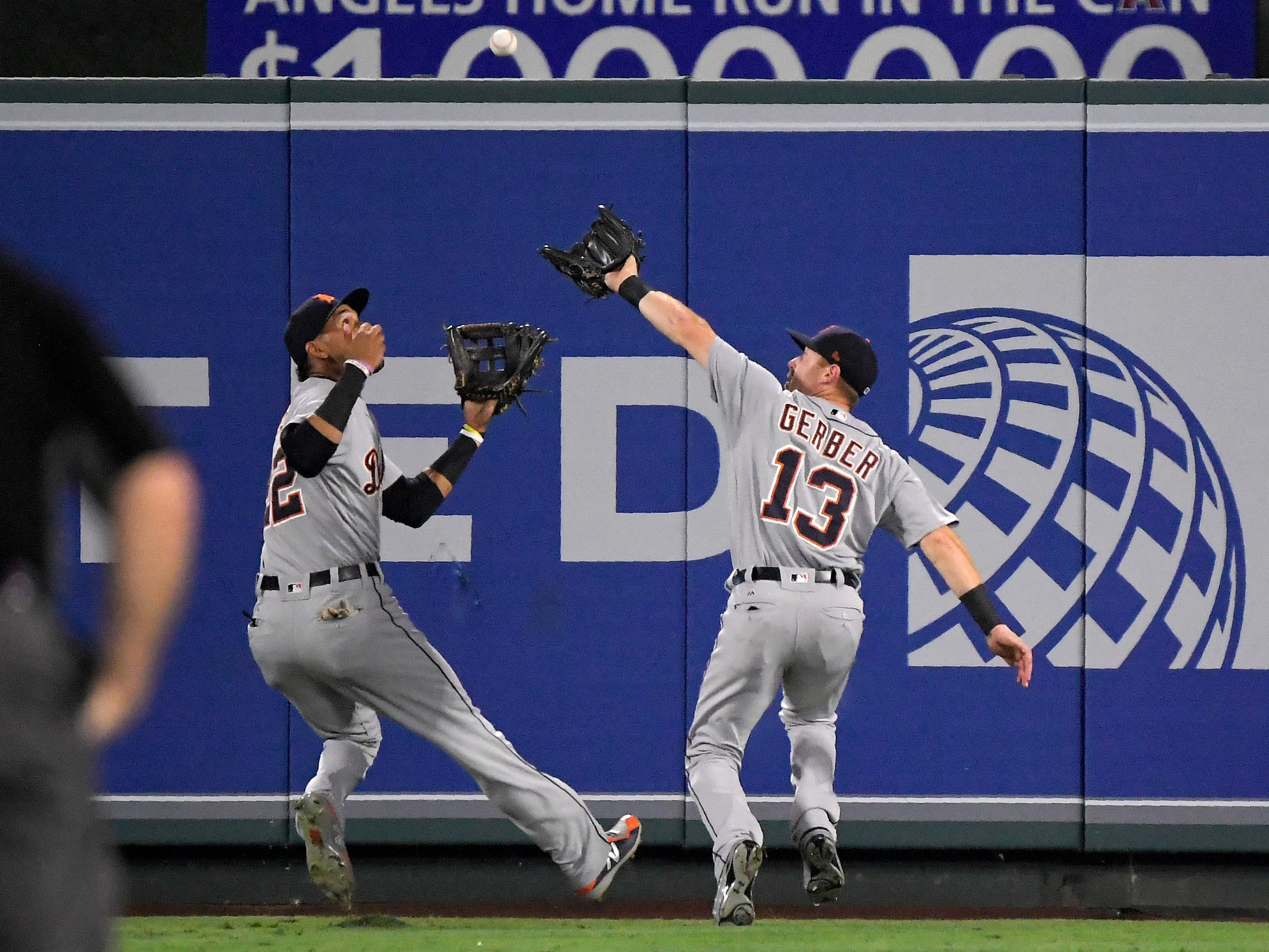 Detroit Tigers center fielder Mike Gerber, right, makes a catch on a ball hit by Los Angeles Angels' Kole Calhoun before colliding with left fielder Victor Reyes during the third inning.