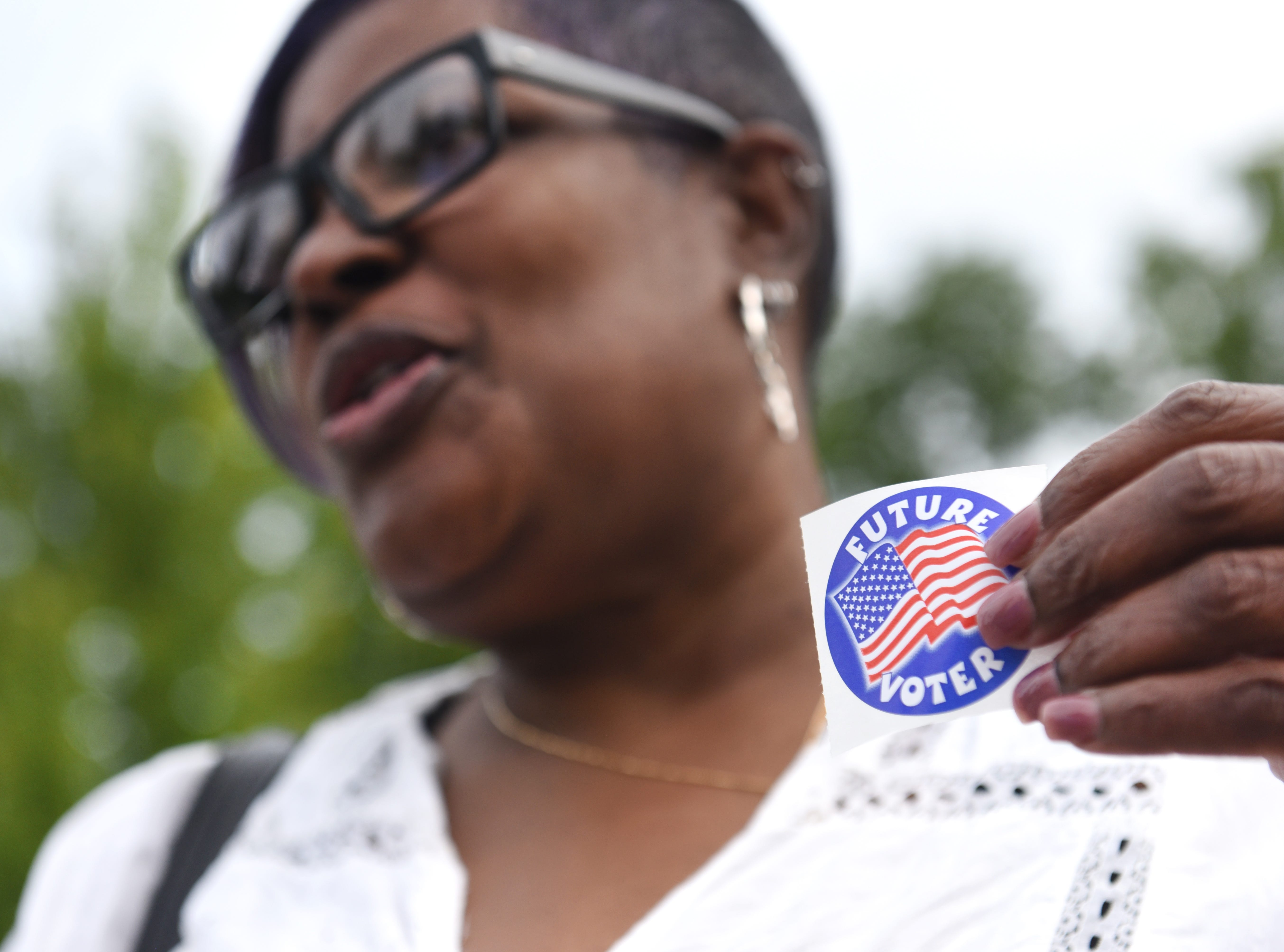 Deborah King of Farmington Hills talks about the importance of voting and holds a sticker for future voters outside Orchard United Methodist Church in Farmington Hills.